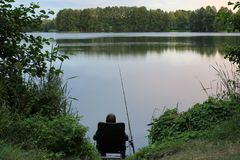 Angler. Sitting on a chair for fishing in a lake royalty free stock photo