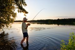 Angler. Standing in a lake and catching the fish during sunset royalty free stock photography