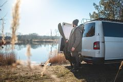 Angler with a camper van moving gear at a lake. A man holding a bag for a fishing rod is standing near a lake. There is a white camper van parked next to him stock image