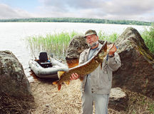 Angler catch big pike fish, fishing with boat. Angler catching big pike fish, fishing on lake with boat royalty free stock photo