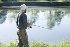 The angler in a hat and wellingtons is standing over the water with a fishing rod. Angler catches fish for spinning. Pulls the fishing line with a spinning royalty free stock photography