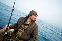 Angler catches a salmon trolling. Angler fisherman catches a salmon trolling in the sea Royalty Free Stock Image