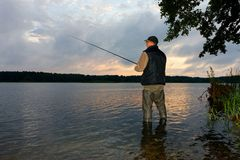 Angler. Catching the fish during cloudy sunrise royalty free stock photos