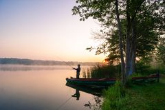 Angler. Catching the fish during misty dawn royalty free stock photos