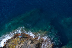 Angler catching fish on rock in Manarola. Royalty Free Stock Photography
