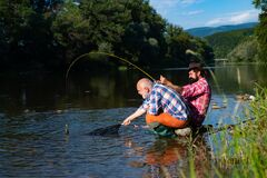 Angler catching the fish. Senior man fishing. Bearded brutal hipsters fishing. Men relaxing nature background. Against