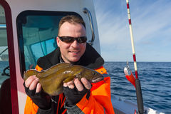 Angler with cusk fish. Sea fishing adventures for a young men Stock Photography