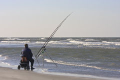 Angler upon dutch beach in Nes, Ameland Island. Angler at the North Sea side of Ameland, one of the West Frisian Islands of the north coast of the Netherlands stock photography