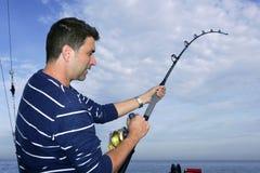 Angler fisherman fighting big fish rod and reel. Saltwater ocean Royalty Free Stock Images