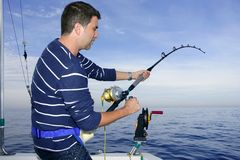 Angler fisherman fighting big fish rod and reel