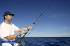 Angler fisherman trolling rod and reel fishing Royalty Free Stock Images
