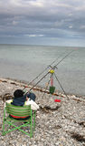 Angler fishing. Angler relaxing in chair fishing from beach in the ocean dark skies looming stock images