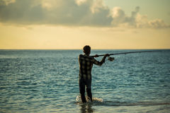 An Angler Fishing on beach. During sunset stock image