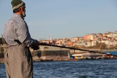 Angler fishing in the city. Old angler fishing amidst the city of Istanbul in Turkey Stock Images
