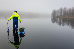 Angler with fishing equipment on the ice Stock Photography