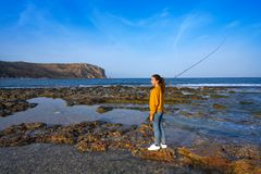 Angler fishing girl in Mediterranean Javea beach. Angler fishing girl with rod in Mediterranean Javea beach at Alicante Spain stock images