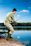 Angler fishing at lake standing on jetty Royalty Free Stock Photography