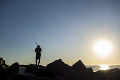 Angler Fishing On The Ocean. Silhouette of a man fishing by the ocean stock photography