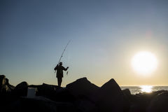 Angler Fishing On The Ocean. Silhouette of a man fishing by the ocean royalty free stock image