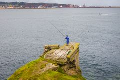 Angler Fishing Off The Cliffs Of Gijon Spain Royalty Free Stock Photography