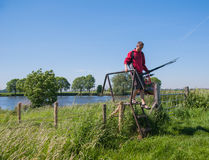 Angler with fishing rod returns from fishing Royalty Free Stock Photography