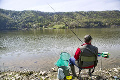 Angler With His Back Towards Camera Sitting On The River Coast Enjoying Angling And Beautiful Nature Royalty Free Stock Photos