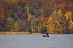 ANGLER ON THE LAKE. Autumn landscape and fisherman in a boat on the lake royalty free stock photos