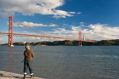 Angler at Lisbon's riverfront. The 25 de Abril Bridge spans the river Tagus and reaches beyond the statue of Cristo Rei. Royalty Free Stock Images