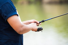 Angler man fishing. Closeup of the angler man hand fishing at the pond stock photography