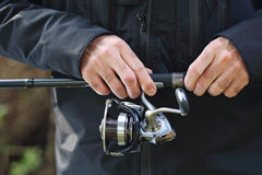 Angler. The man holds an fishing reel in his hands royalty free stock image