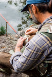 Angler. Man sitting by the water holding fish royalty free stock images