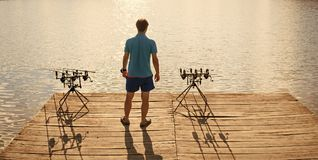 Angler man stand on wooden pier, back view. Fisherman fishing with spinning rods, reels at lake water. Summer vacation, adventure, activity. Fishing, angling stock image