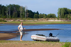 Angler with motor boat on the riverbank Royalty Free Stock Images