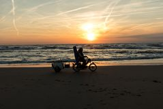 Angler riding a bicycle on beach in Katwijk at sunset. Netherlands stock image