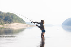 Angler in the river. A fisherman with a spinning rod on the river stock photo