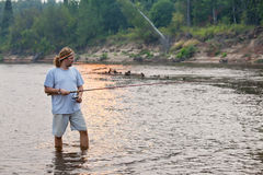 Angler on the river. A fisherman with a spinning rod on the river stock photography