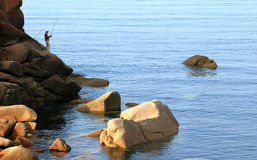 Angler upon the rocks of the Pink Granite Coast in Bretagne Royalty Free Stock Photo