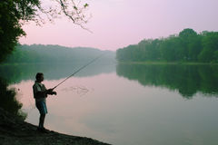 Angler's summer dawn. A man fishing from the river bank in the early morning light stock photos
