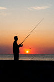 Angler. Silhouette against the sunset stock photos
