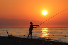 Angler in silhouette catch the sunrise Stock Photo