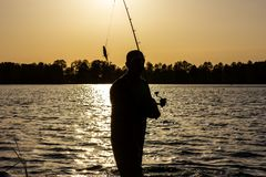 Angler. Silhouette of angler during sunset royalty free stock images