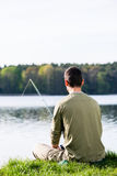 Angler sitting in grass at lake fishing with his rod Stock Photography