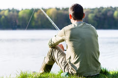 Angler sitting in grass at lake fishing with his rod. A very peaceful scene royalty free stock images