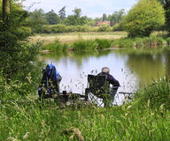 Angler sitting by a Lake. Man fishing on the banks of a lake in Rural England stock image