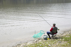 Angler Sitting On The River Coast And Patiently Waiting For Fish To Take A Bait Royalty Free Stock Photos