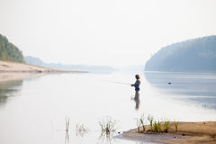 Angler with spinning on the river Stock Photography