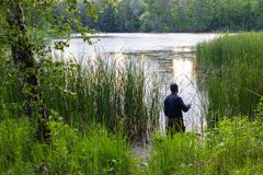 Angler. Standing in the lake and catching the fish stock images