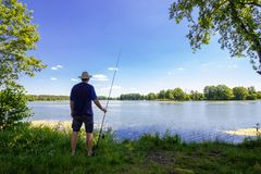 Angler. Standing on the lake shore during summer day royalty free stock photo