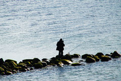Angler on stones sillhouette Stock Image
