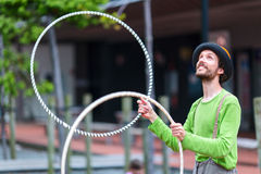 Angler on the street is playing with colorful rings. Auckland city, New Zealand. Royalty Free Stock Image
